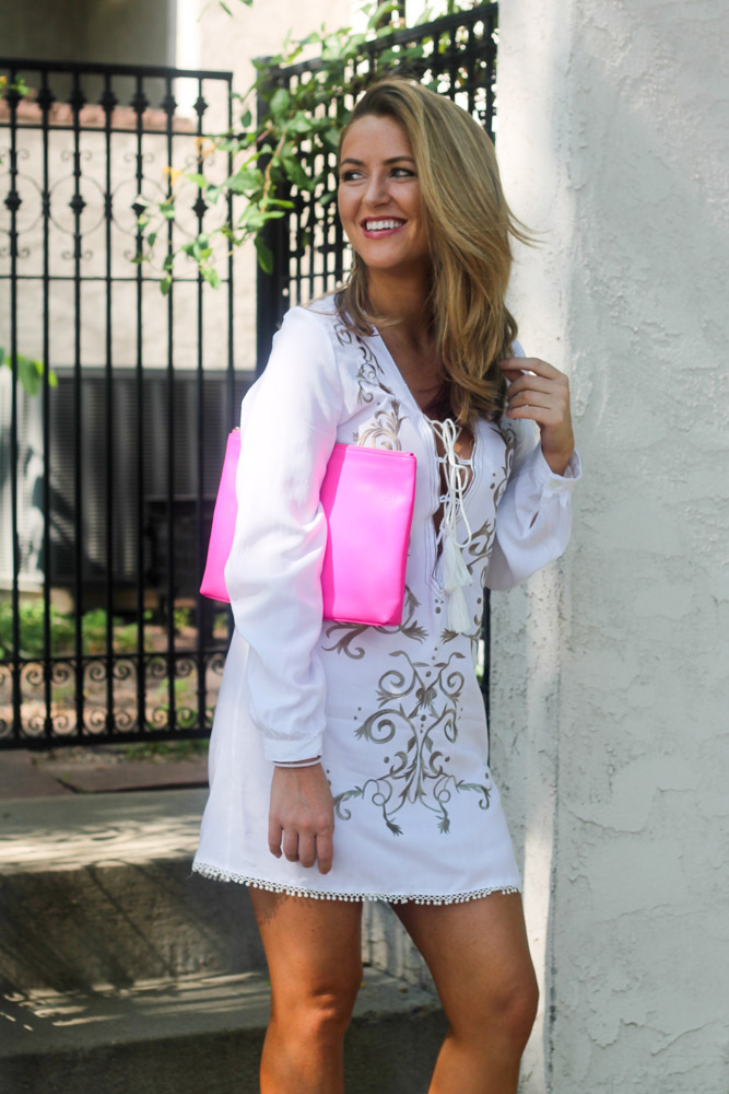 Amber from Every Once in a style wearing a white lace up embroidered dress and hot pink clutch
