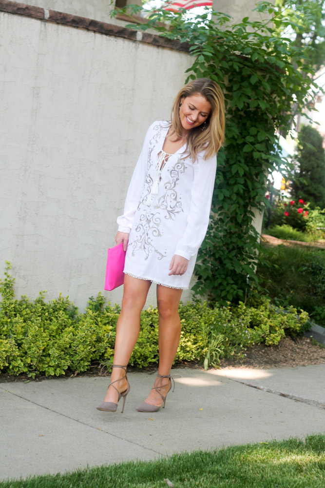 Amber from Every Once in a style wearing a summer look in a white lace up embroidered dress and hot pink clutch