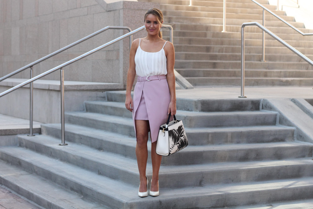 amber from every once in a style wearing a chic wish pink belted skirt and white pumps
